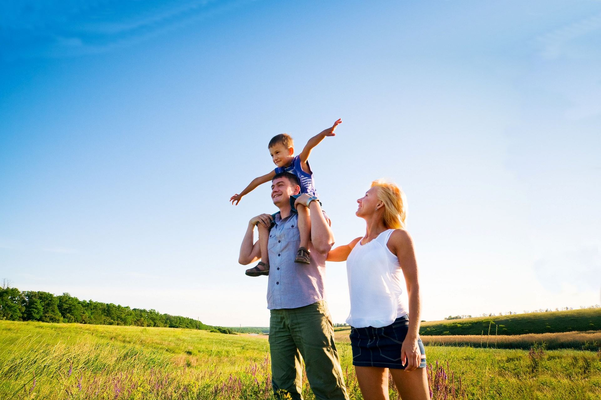 Family standing in a green field with the son on the father's shoulders holding his arms out
